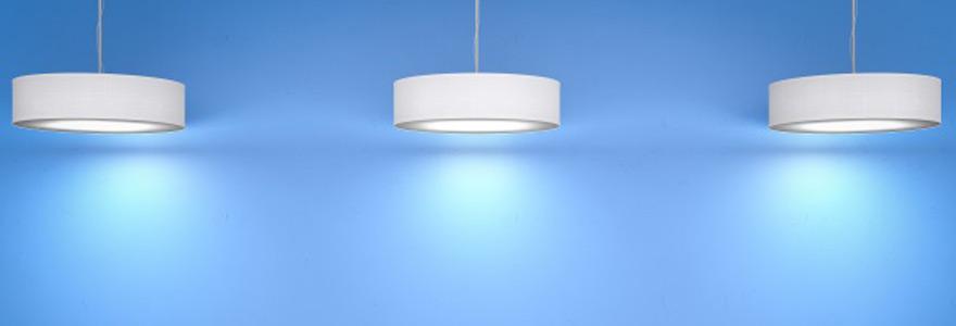 Trois plafonniers LED blancs suspendus sur fond bleu